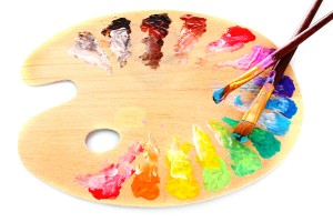 wooden art palette with blobs of paint and a brush on white background